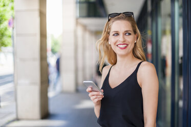 Portrait of smiling young woman with smartphone watching something - DIGF000746