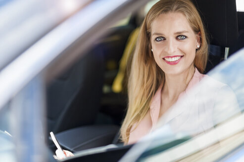 Portrait of smiling young businesswoman sitting in a car - DIGF000755