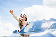 Portrait of smiling young woman with eyes closed leaning out of car window - DIGF000758
