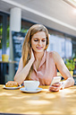 Portrait of smiling woman sitting in a sidewalk cafe looking at her smartphone - DIGF000761