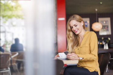 Smiling young woman sitting in a coffee shop looking at smartphone - DIGF000764