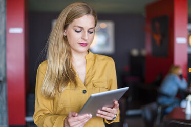 Businesswoman in a coffee shop looking at her tablet - DIGF000767