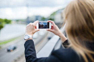 Back view of woman standing on a bridge taking photo with smartphone - DIGF000773