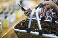 Close-up of woman holding shopping basket and cell phone - ZEF009093