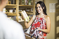 Woman holding product in health shop - ZEF009096