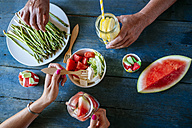 Close-up of hands eating salad, watermelon, lemonade, asparagus and candy - KIJF000595