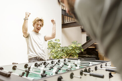 Colleagues playing table football in office - PESF000202