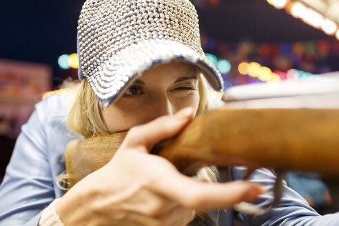 Young woman at fun fair shooting at shooting gallery - PES000229