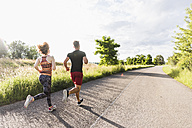 Young couple running on country road - UUF008084