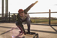 Young man riding skateboard on parking level - UUF008108