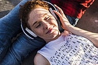 Young woman with headphones lying on boyfriend's lap - UUF008114