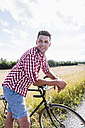 Smiling young man with bicycle in nature - UUF008138