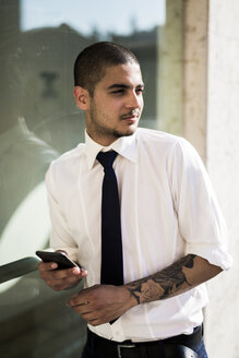 Portrait of young businessman with smartphone looking at distance - GIOF001256