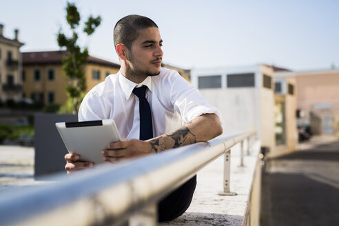 Young businessman with tablet looking at distance - GIOF001259