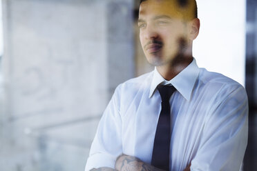 Serious young businessman behind glass pane - GIOF001262