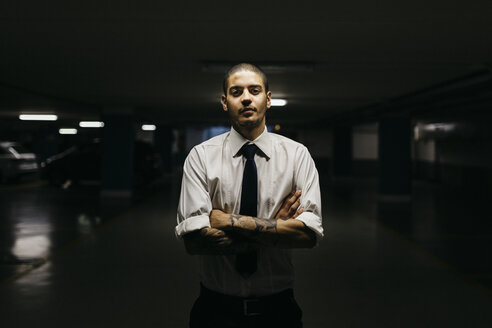 Portrait of young businessman standing in a gloomy car park - GIOF001265