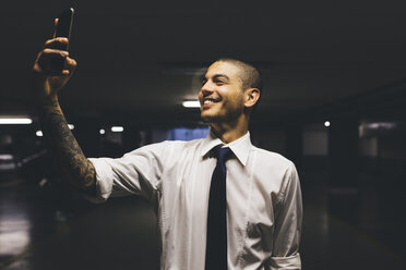 Smiling young businessman standing in a gloomy car park taking a selfie with cell phone - GIOF001268