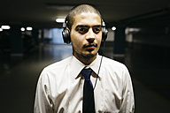 Portrait of young businessman with headphones in a gloomy car park - GIOF001271