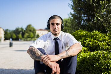 Young businessman listening music with headphones - GIOF001274