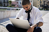 Smiling young businessman looking at laptop - GIOF001280