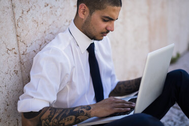 Serious young businessman sitting on the ground using his laptop - GIOF001283
