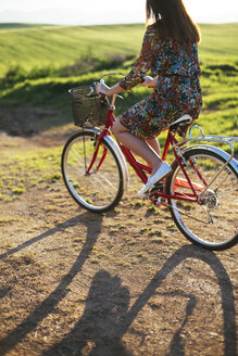 Young woman wearing dress with floral design riding bicycle on a dirt track - DERF000039