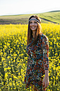 Portrait of happy young woman standing in a rape field - DERF000042