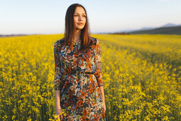 Portrait of young woman standing in a rape field - DERF000051