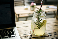 Homemade lemonade and laptop on table in a cafe - ONF000926