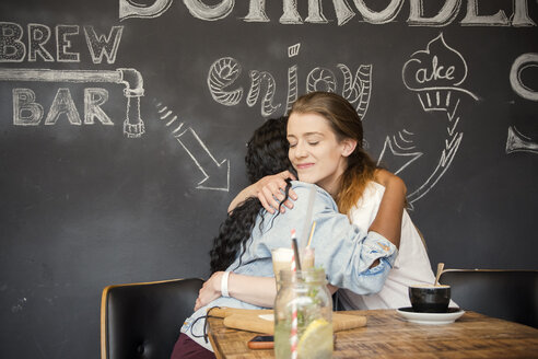 Two friends meeting in cafe, embracing - ONF000947