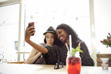 Two young women taking selfie in a cafe - ONF000965