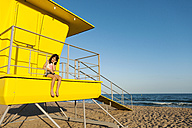 Little girl sitting on a yellow lifeguard stand at the beach - VABF000700