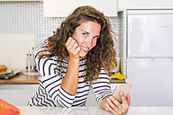 Portrait of smiling woman with smartphone in the kitchen - SIPF000647
