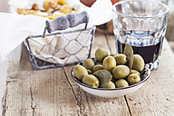 Tapas, green olives in bowl, red wine glass on wood - SBDF003036