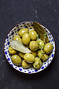 Green olives thyme and bay leaves in bowl - SBDF003039