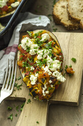 Filled aubergine with bell pepper, tomato, courgette, sheep cheese and parsley on chopping board - ODF001413