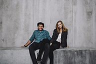 Young couple sitting in front of concrete wall, smiling - GCF000212
