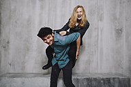 Young couple sitting in front of concrete wall, piggyback - GCF000218