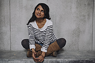 Female Indian sitting on concrete wall - GCF000227
