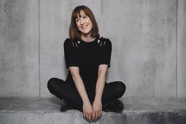 Woman smiling, sitting on concrete wall - GCF000230