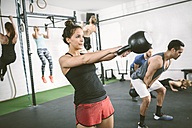 People in gym training with kettle bells - MAD000988