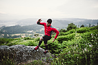 Trail runner man training in nature, on a rock - RAEF001310