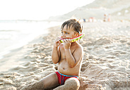 Little boy sitting on the beach at seafront eating watermelon - VABF000703