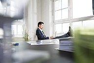 Businessman sitting with feet up and laptop on his lap - FKF001946