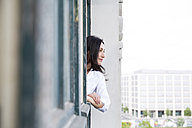 Businesswoman looking out of window - FKF001970
