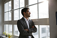 Businessman standing at the window with arms crossed - FKF001985