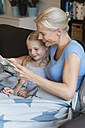 Mother and little daughter sitting on couch reading a book together - MIDF000760