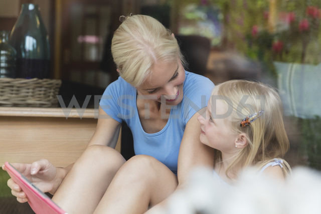 Mother and little daughter sitting behind window pane looking at each other - MIDF000763