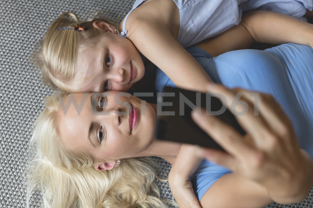 Mother and her little daughter lying on the floor taking selfie with smartphone - MIDF000766 - Miriam Dörr/Westend61