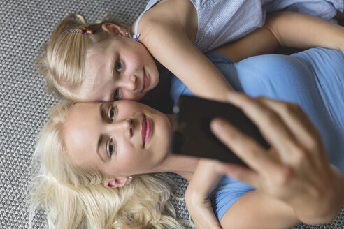 Mother and her little daughter lying on the floor taking selfie with smartphone - MIDF000766